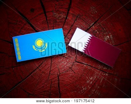 Kazakhstan Flag With Qatari Flag On A Tree Stump Isolated