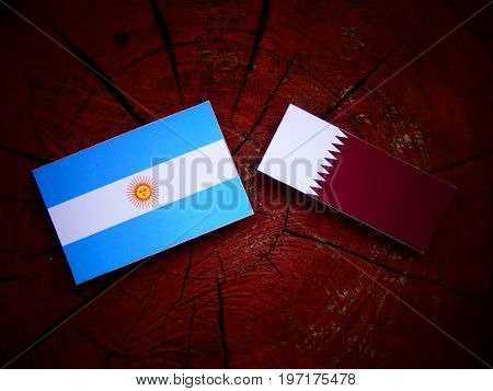Argentinian Flag With Qatari Flag On A Tree Stump Isolated