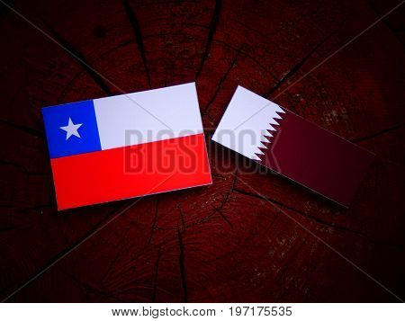 Chilean Flag With Qatari Flag On A Tree Stump Isolated