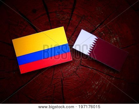 Colombian Flag With Qatari Flag On A Tree Stump Isolated