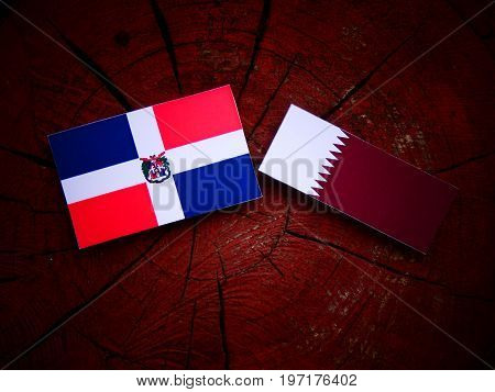 Dominican Republic Flag With Qatari Flag On A Tree Stump Isolated
