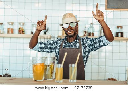 Cheerful Stylish African American Bartender Gesturing And Standing At Bar Counter With Lemonades