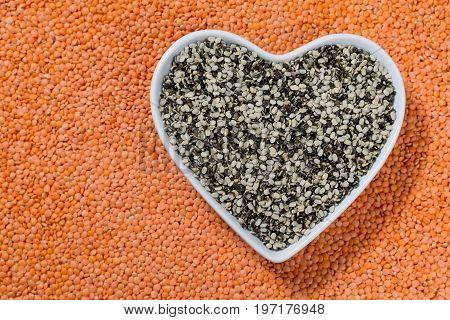Heart Form Bowl With Black Lentils Over Red Lentils Background