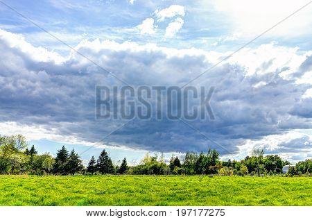 Stormy Large Gray Cloudscape With Green Sheep Pasture During Summer