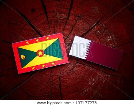 Grenada Flag With Qatari Flag On A Tree Stump Isolated