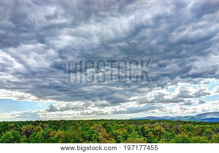 Stormy Large Gray Cloudscape With Green Forest During Summer