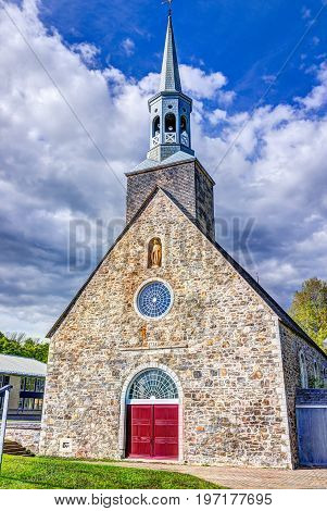 Ile D'Orleans Canada - June 1 2017: Saint-Francois red painted church with stone architecture and gold statue blue sky in summer