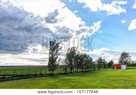 Red Painted Vintage Shed With Doors In Summer Landscape Field In Countryside With Fence And Sun Rays