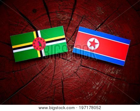 Dominica Flag With North Korean Flag On A Tree Stump Isolated