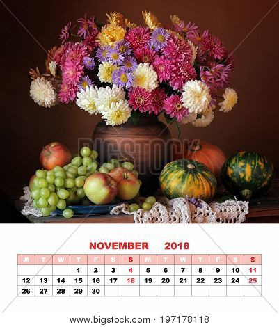 Page design calendar November 2018. Autumn still life with a bouquet of chrysanthemums green grapes apples and pumpkins against a dark background.