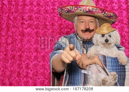 a man wears a sombrero and holds his white dog wearing a costume in a photo booth against a hot pink background.