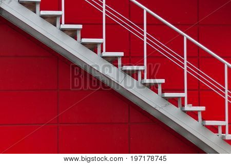 gray metal stair on the red wall. minimalism concept.