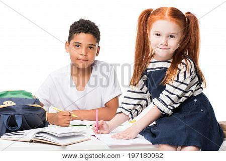 Happy Multiethnic Schoolkids Studying Together And Looking At Camera Isolated On White