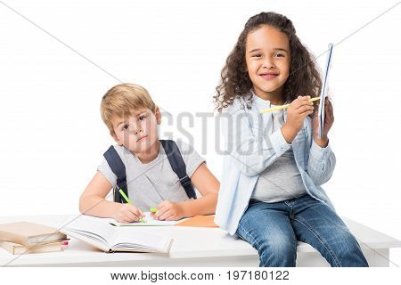 adorable multiethnic schoolkids studying together and looking at camera isolated on white