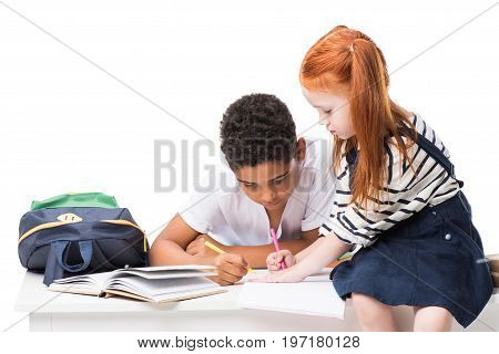 cute focused multiethnic schoolkids studying together isolated on white
