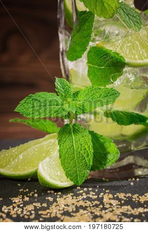 Close-up of a tasty organic beverage with fresh slices of lime, ice and leaves of mint, on a wooden background. Summer beverages.