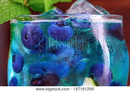 Close-up of blue fresh beverage  on the wooden background. Refreshing bright blue lagoon cocktail with mint, bilberries and ice in transparent highball glass. Refreshing blue summer cocktail.