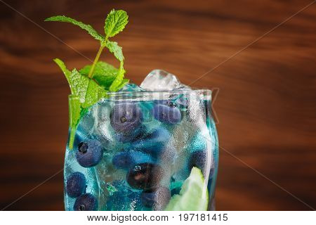 Close-up of fresh beverage on the wooden background. Refreshing bright blue lagoon cocktail with lime slice, mint, bilberries and ice in transparent highball glass. Refreshing blue summer cocktail.