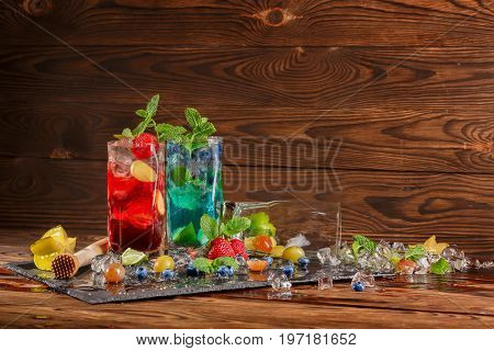 Refreshing blue and red beverages on a black table-napkin. Colourful cocktails with mint, slices of lime, berries, ice and carambola in transparent highball glasses on the wooden background.