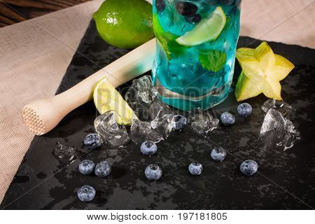 Close-up of blue fresh beverage on a black table-napkin and wooden table. Refreshing bright blue lagoon cocktail with slices of lime, bilberries, ice and carambola in transparent highball glass.