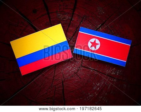 Colombian Flag With North Korean Flag On A Tree Stump Isolated