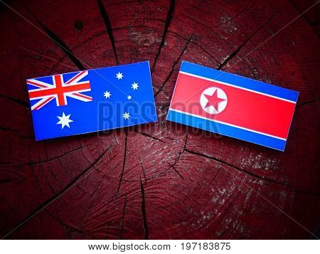 Australian  Flag With North Korean Flag On A Tree Stump Isolated