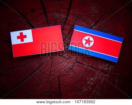 Tongan Flag With North Korean Flag On A Tree Stump Isolated