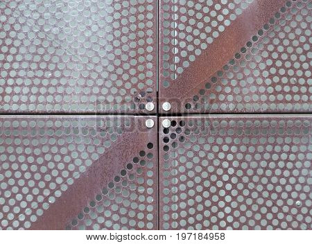 iron metal sheet plate cladding with perforated holes in a geometric pattern and a rust effect