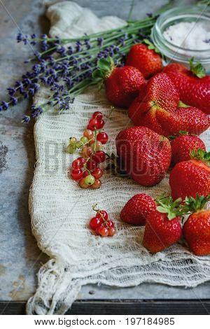Fresh ripe strawberries prepared for making jam. Served with sugar, lavender, red currant on gauze over gray metal background. Preserving concept. Rustic style, day light