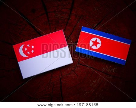 Singaporean Flag With North Korean Flag On A Tree Stump Isolated