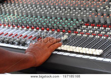 Male's hand adjusting audio mixer (music sound audio)