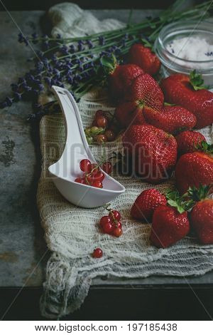 Fresh ripe strawberries prepared for making jam. Served with sugar, lavender, red currant and big white plastic spoon on gauze over gray metal background. Preserving concept. Rustic style, day light