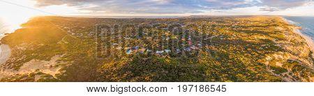 Aerial panorama of luxurious vacation homes in lush coastal vegetation at sunset. Morningon Peninsula Melbourne Australia