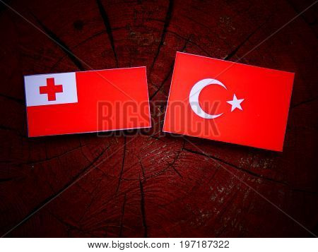 Tongan Flag With Turkish Flag On A Tree Stump Isolated