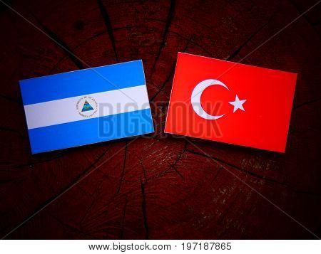 Nicaraguan Flag With Turkish Flag On A Tree Stump Isolated