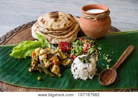 Homemade nutritional vegetable ragout rice salad yogurt chapati on a banana leaf. Home cooked indian vegetable stew sabji. Thali for gourmet. Vegan and vegetarian food. Selective focus.