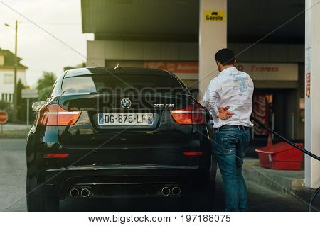 PARIS FRANCE - MAY 7 2016: Adult man refueling at the gas station his BMW X6 M sport suv with sun flare light leak