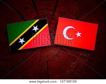 Saint Kitts And Nevis Flag With Turkish Flag On A Tree Stump Isolated