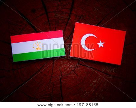 Tajikistan Flag With Turkish Flag On A Tree Stump Isolated