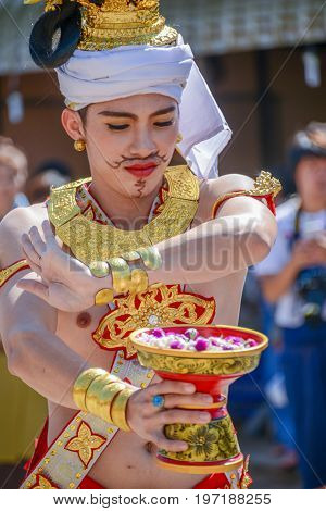 CHIANGMAI THAILAND - JANUARY 25 2015: Indigenous dancer man with traditional costume holding tray with pedestal of flower dancing in parade of 22nd Traditional Skirt Fabric and The Indigenous Product and Culture Festival in Mae Chaem Chiangmai Thailand