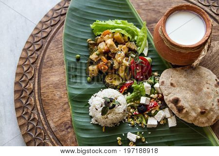 Homemade nutritional vegetable ragout rice salad yogurt chapati on banana leaf. Home cooked indian vegetable stew sabji. Thali for gourmet. Vegan and vegetarian food. Selective focus.