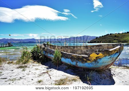 Photograph full of contrasts in blue with a boat deteriorated by the passage of time.
