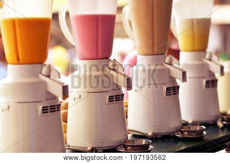 Row of blenders with fresh smoothies close-up