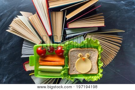 Some books with lunche box on the desk over the blackboard
