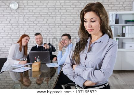 Portrait Of A Sad Businesswoman With Colleagues Laughing On Her In Background
