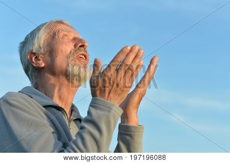 Portrait of senior man against blue sky