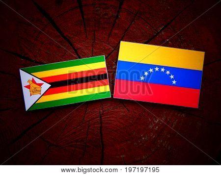 Zimbabwe Flag With Venezuelan Flag On A Tree Stump Isolated