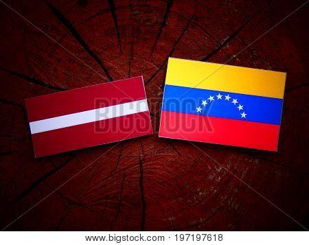 Latvian Flag With Venezuelan Flag On A Tree Stump Isolated