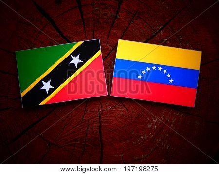 Saint Kitts And Nevis Flag With Venezuelan Flag On A Tree Stump Isolated