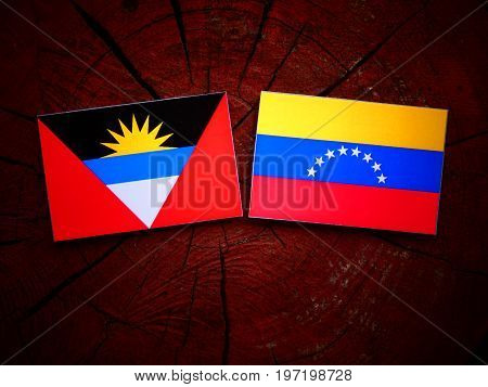 Antigua And Barbuda Flag With Venezuelan Flag On A Tree Stump Isolated